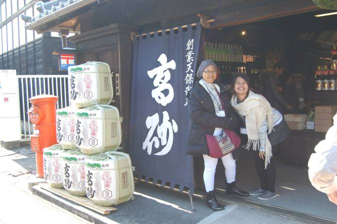 Joyce and I with the sake barrels at Fuji Takasago Sake Brewery store entrance (Photo credit: Song Dimacale)